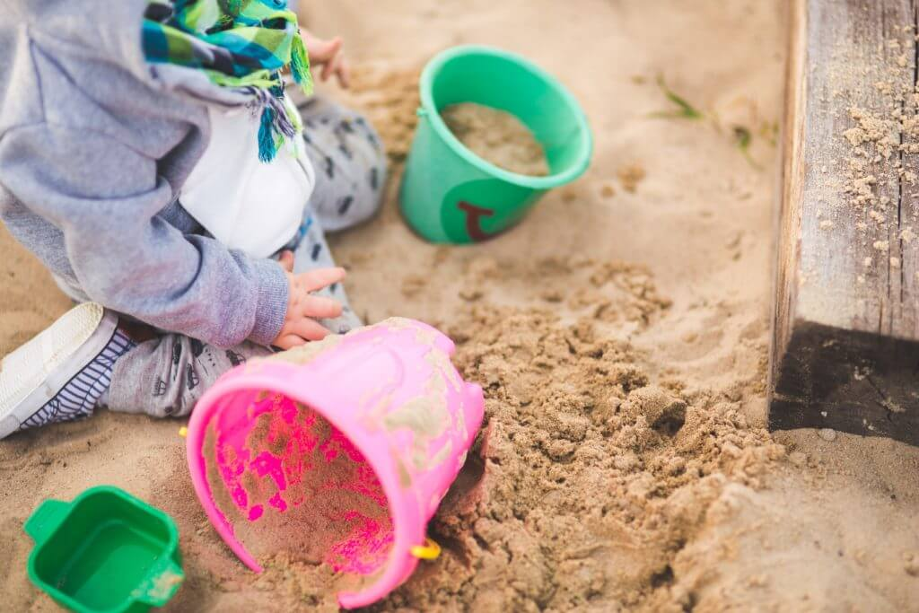 Buckets and sand with young child
